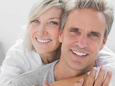 Middle-aged couple smiling & hugging l Dentures Fayetteville AR