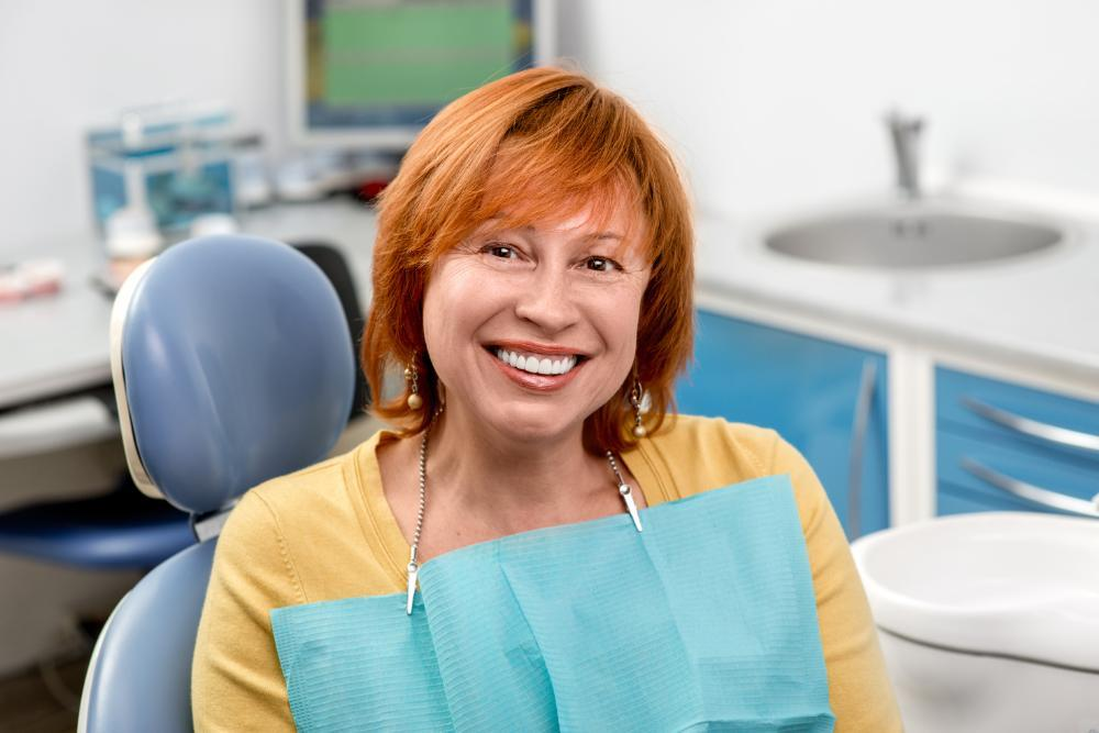 woman sitting in dental exam chair smiling brightly I dental exam fayetteville ar