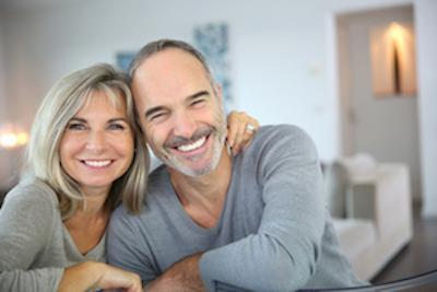 older couple smiling & hugging with bright smiles I same-day dental crowns fayetteville ar