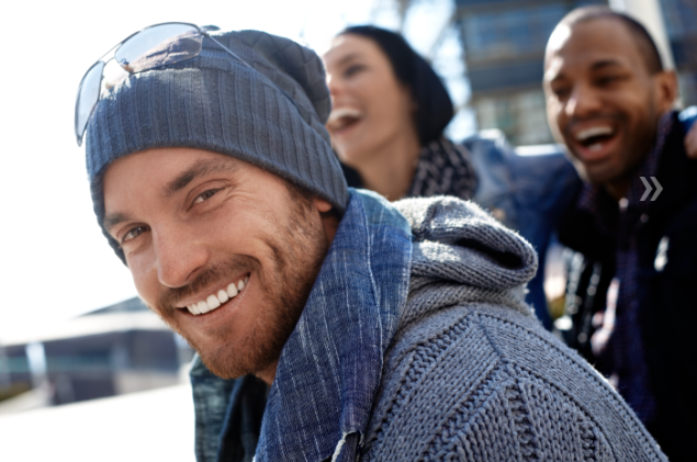 man in cold weather clothing with bright smile I teeth whitening at northwest arkansas family dental