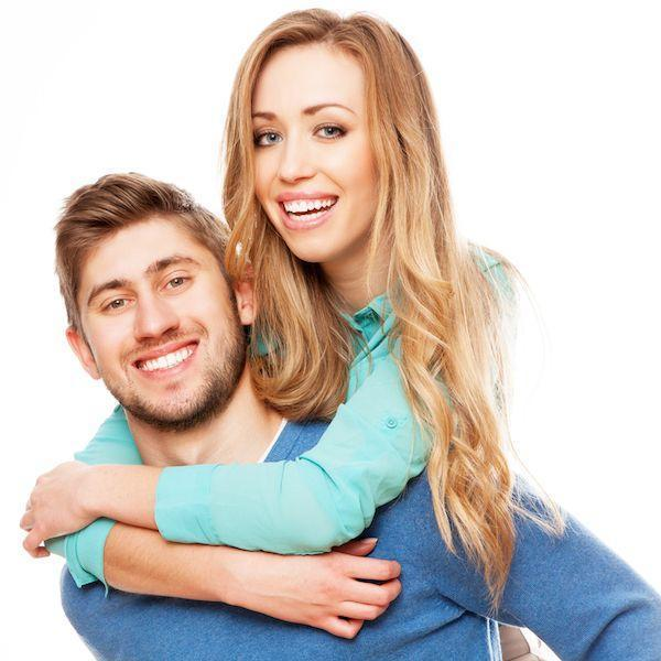 Young couple smiling and hugging I Cosmetic Dentist in Fayetteville AR