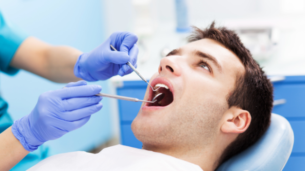 Man receiving dental exam l Northwest Arkansas Family Dental
