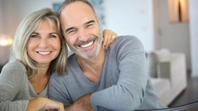 Older couple hugging & smiling l Dental implants Fayetteville AR